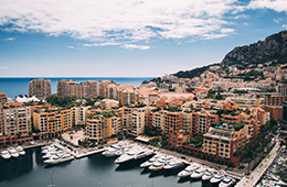 MonteCarlo view of docks with yachts and ocean with buildings on the hiillside