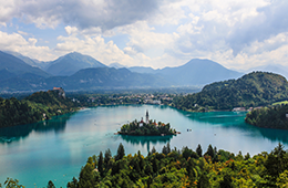 Landscape of Lake Bled with an island in the middle which has buildings, background includes more mountains