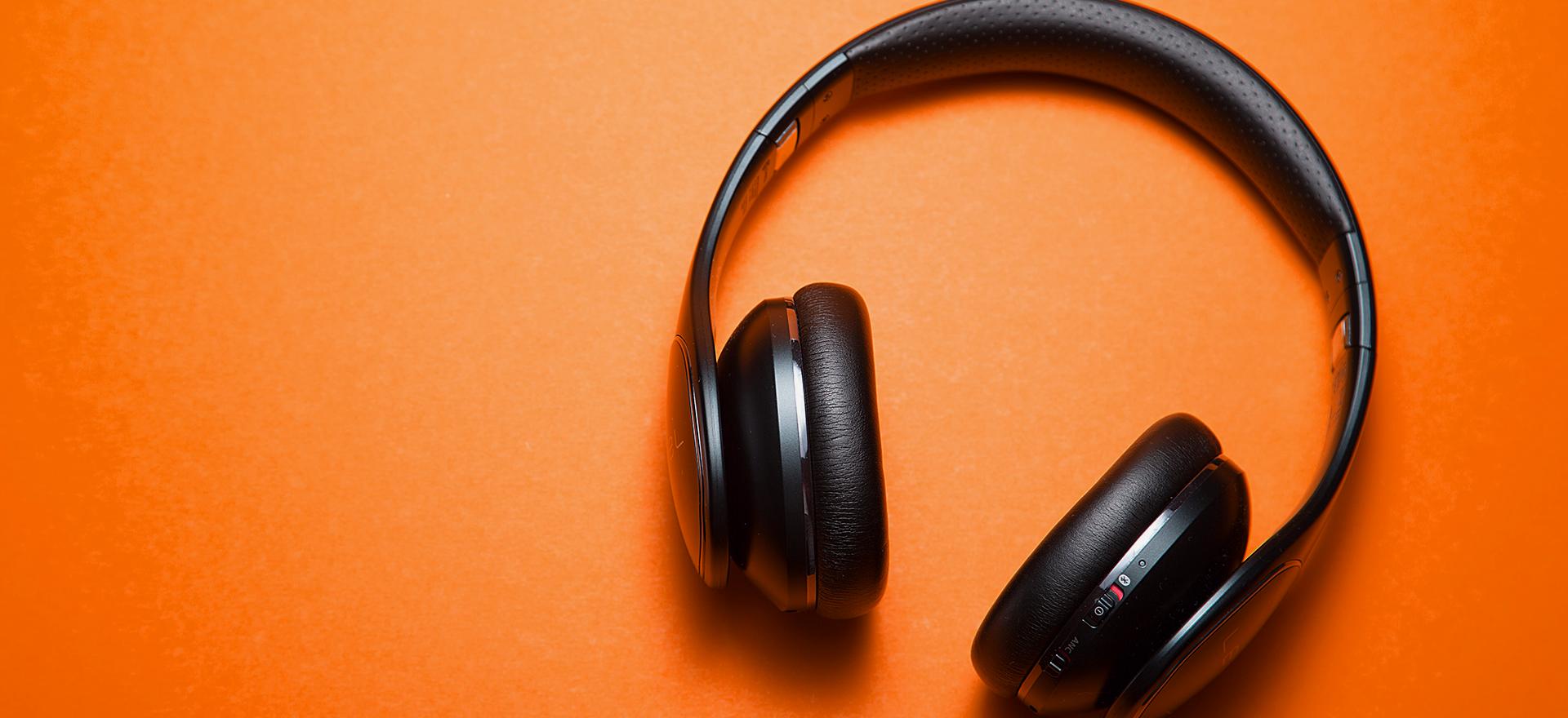 Black headphones on an orange background