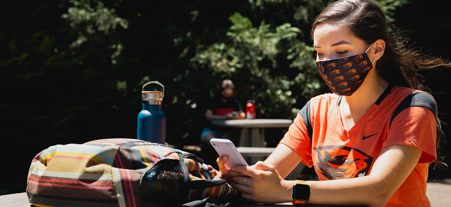 A student in a beaver shirt with a beaver mask looking at her phone at a table.