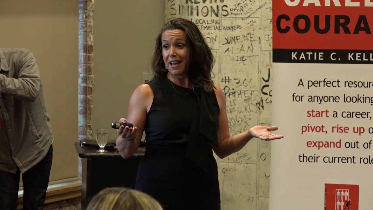 Katie Kelly speaking next to signage at an event